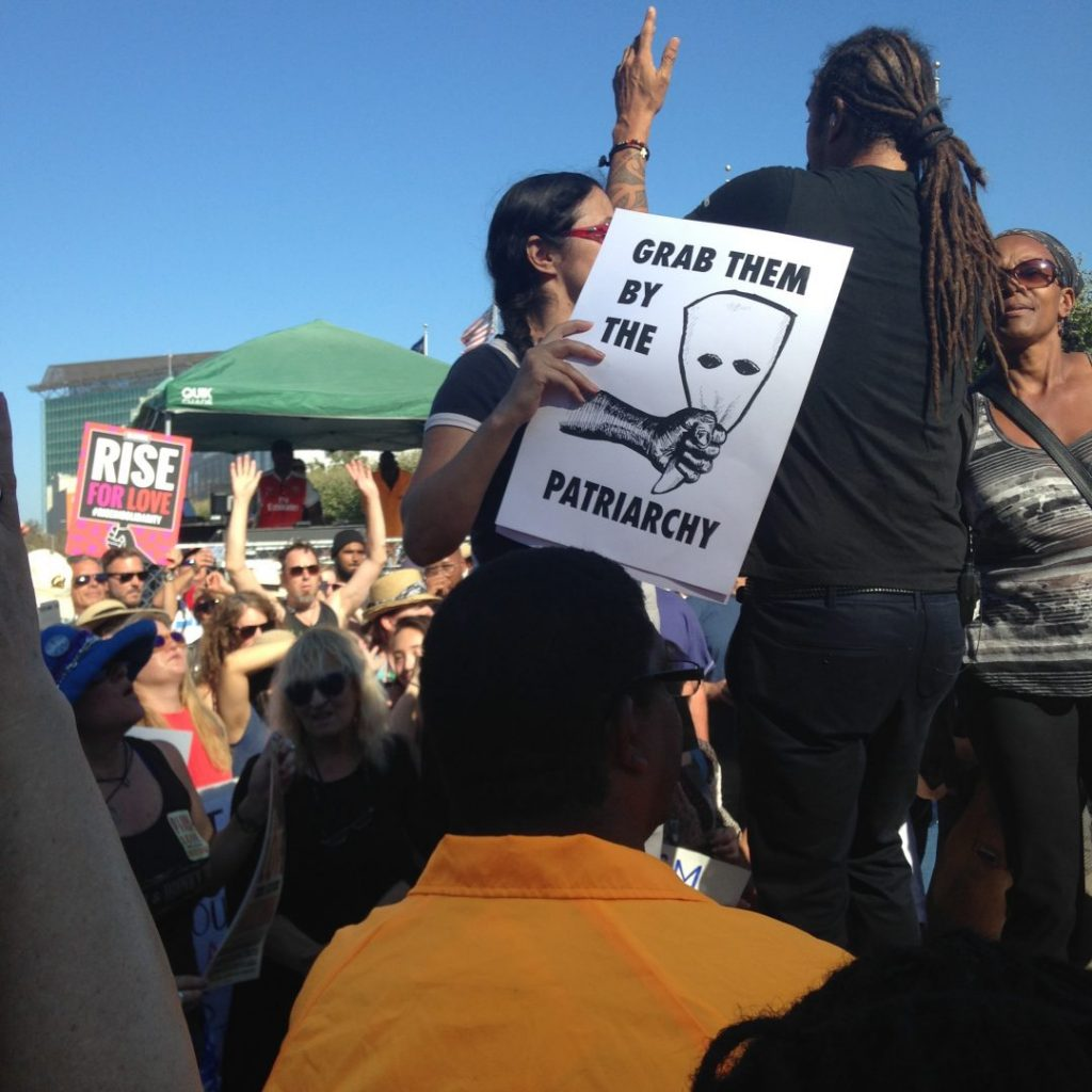 Rally participant dancing with sign and Michael Franti. Copyright 2017 by the Sonoma Independent.org. Free to share with attribution